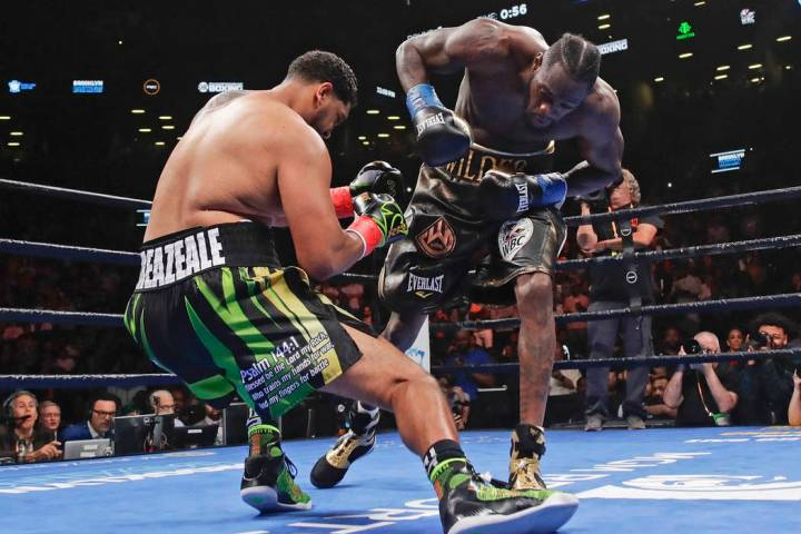 Deontay Wilder, right, knocks down Dominic Breazeale during the first round of the WBC heavywei ...