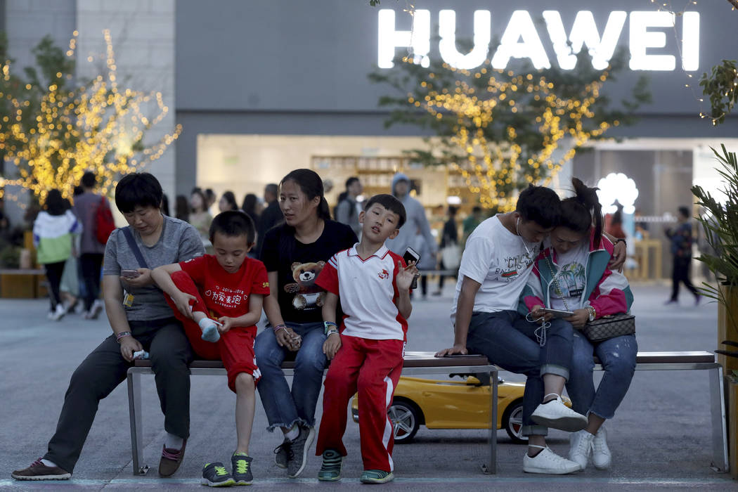 In a photo taken Monday, May 20, 2019, residents enjoy a cool evening near a Huawei store in Be ...