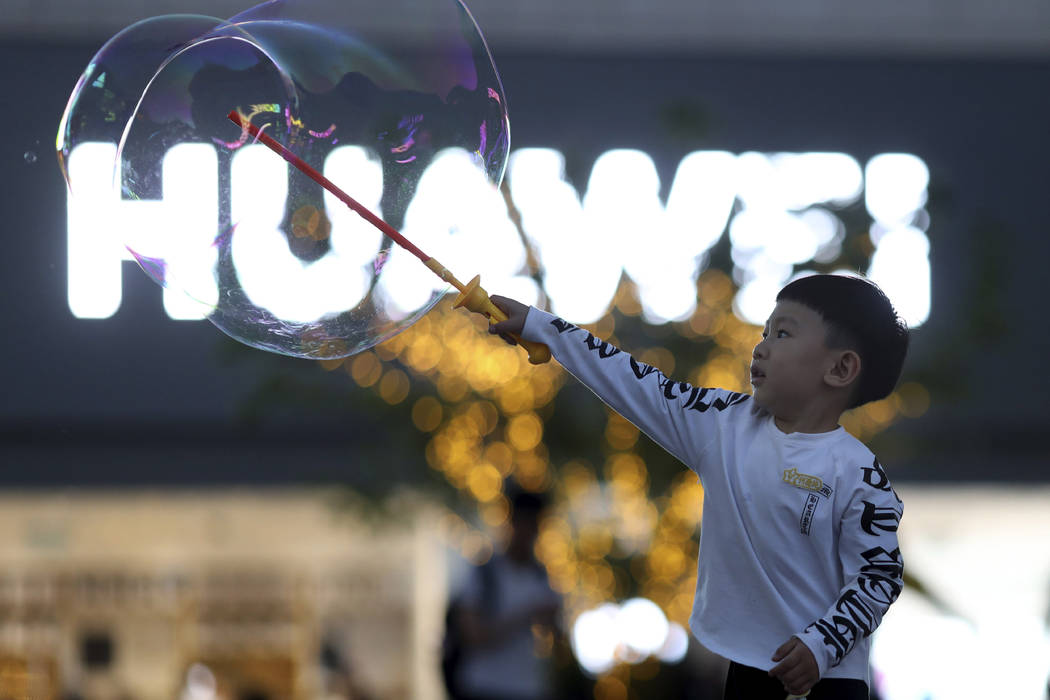 In this photo taken Monday, May 20, 2019, a child plays with bubbles near the logo for tech gia ...
