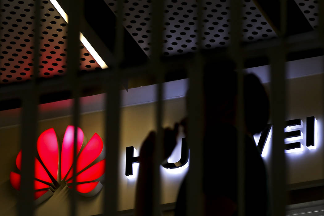 A man walks by a Huawei retail shop behind a handrail inside a commercial office building in Be ...