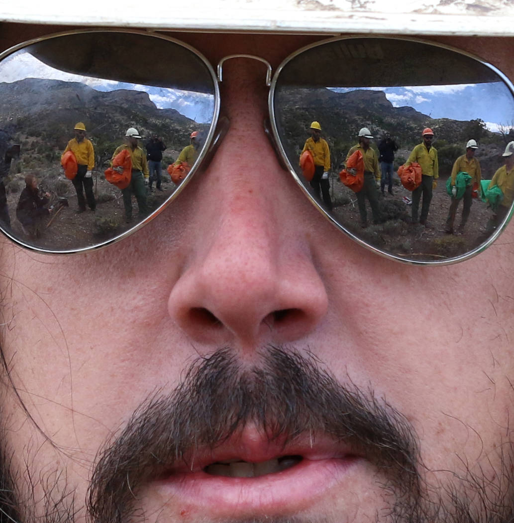 Firefighters from Bureau of Land Management are reflected in the sunglasses of Andrew Merriam, ...
