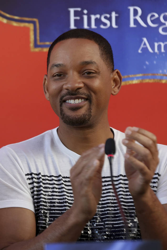 U.S. actor Will Smith applauds during a news conference with the director Guy Ritchie and stars ...
