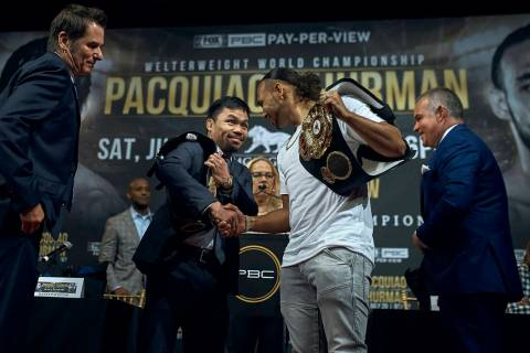 Manny Pacquiao, center left, shakes hands with Keith Thurman, center right, during a news confe ...