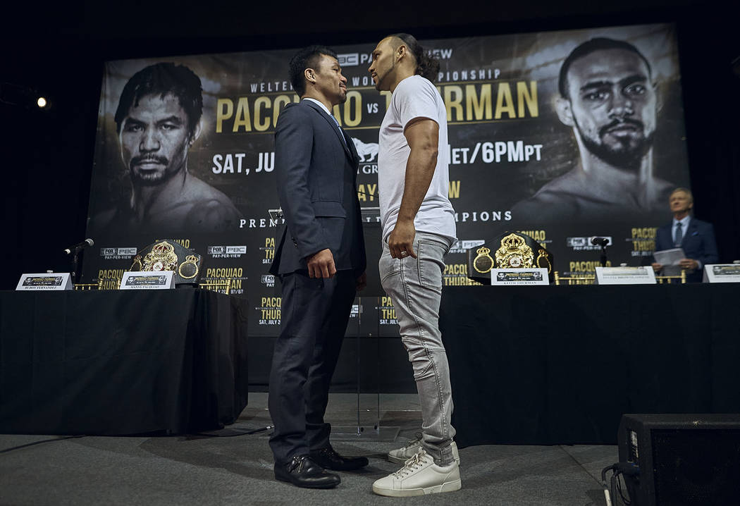 Manny Pacquiao, left, and Keith Thurman stand face to face during a news conference, Tuesday, M ...