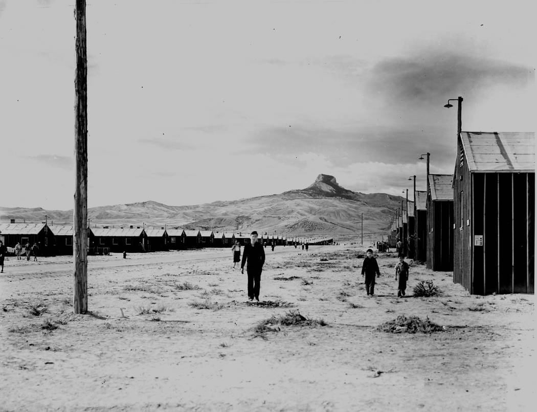 Three men are seen standing outside the barracks at the internment camp near Heart Mountain in ...