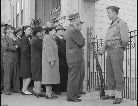 People wait to register as an armed guard watches in this undated photo. Sam Mihara showed it d ...