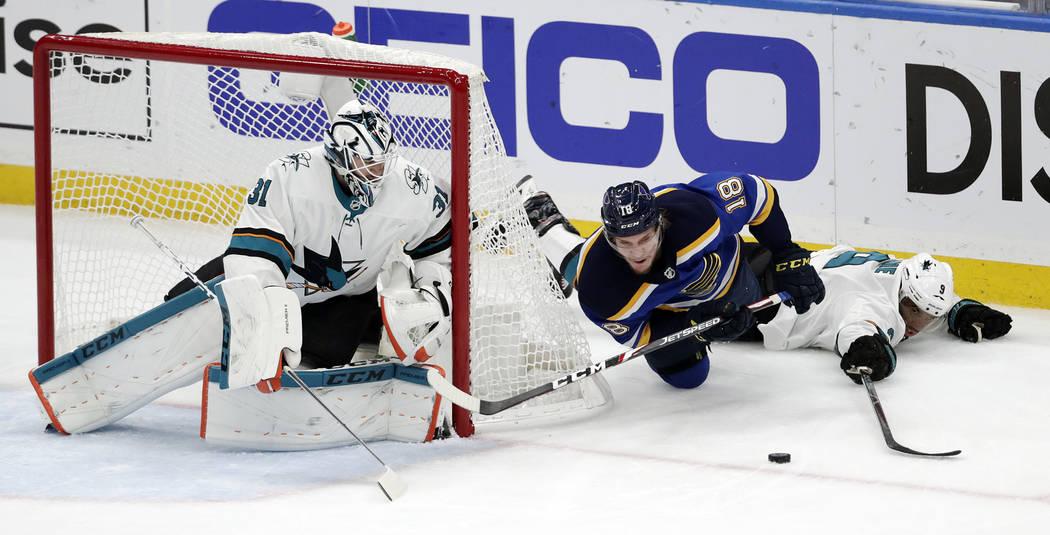 St. Louis Blues center Robert Thomas (18) falls as he chases the puck between San Jose Sharks g ...