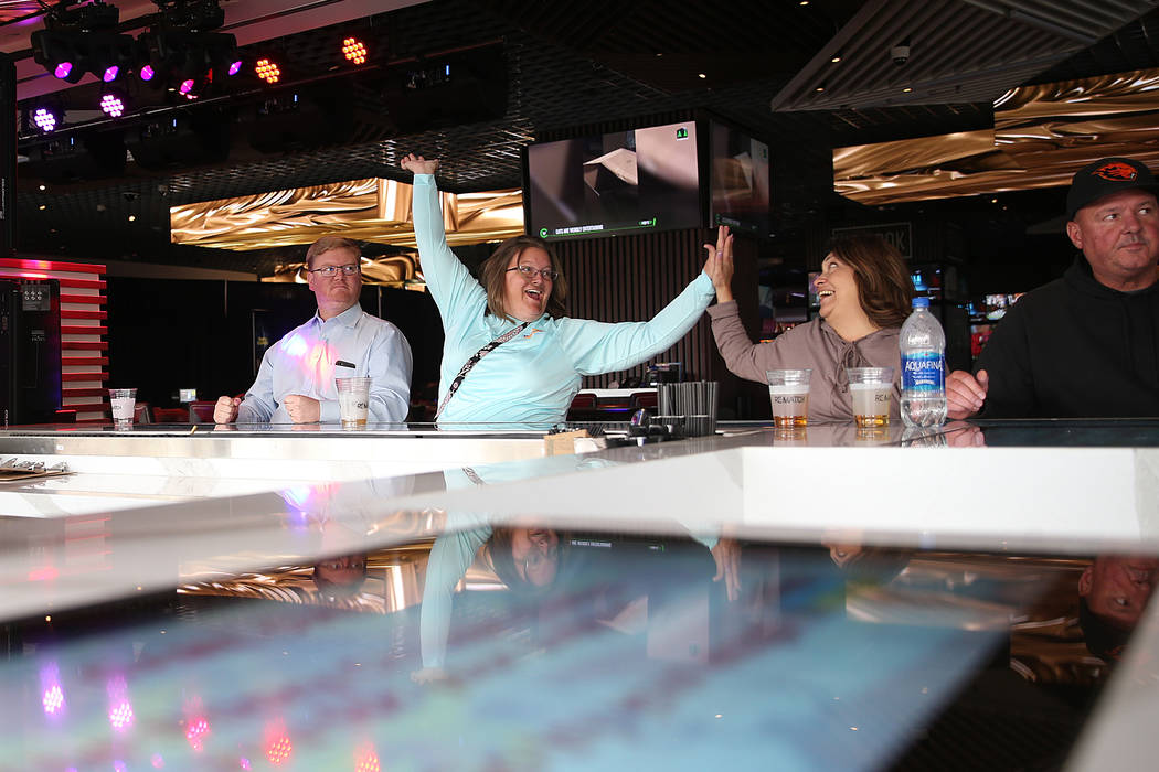 Jason Hessler, from left, looks on as his wife Marjorie, of Indiana, reacts after winning a bar ...