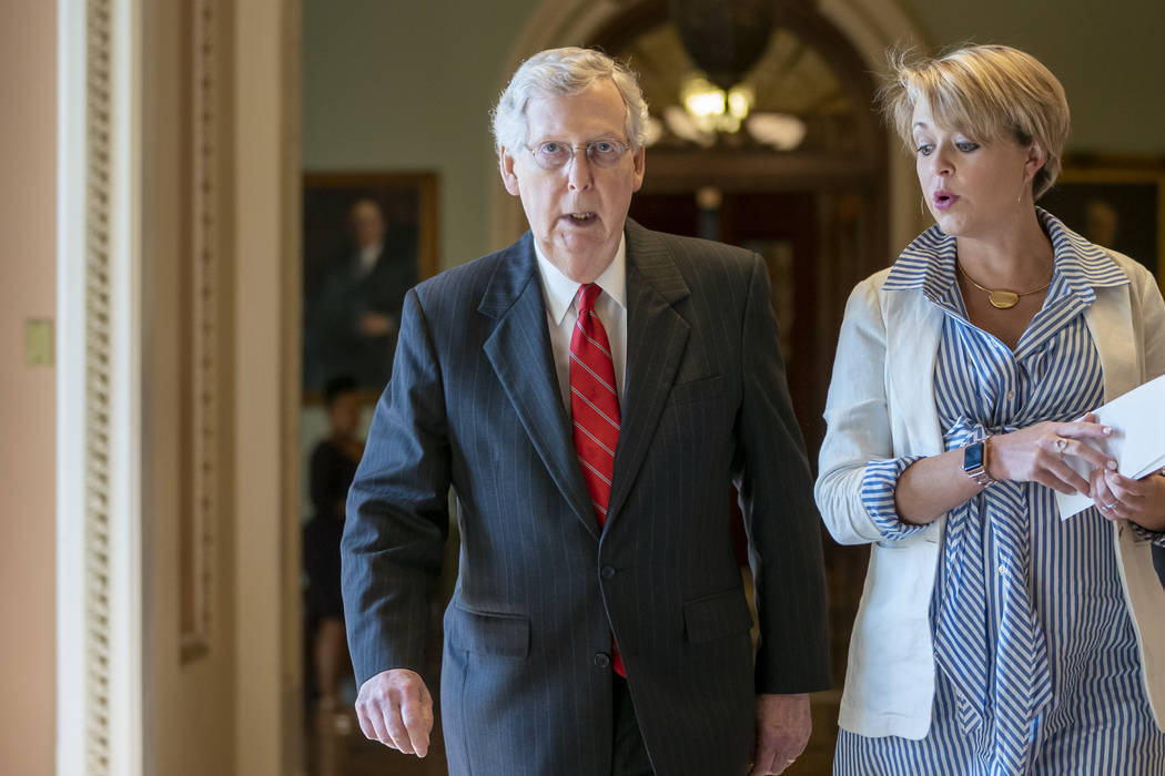 Senate Majority Leader Mitch McConnell, R-Ky., joined at right by aide Stefanie Hagar Muchow, w ...