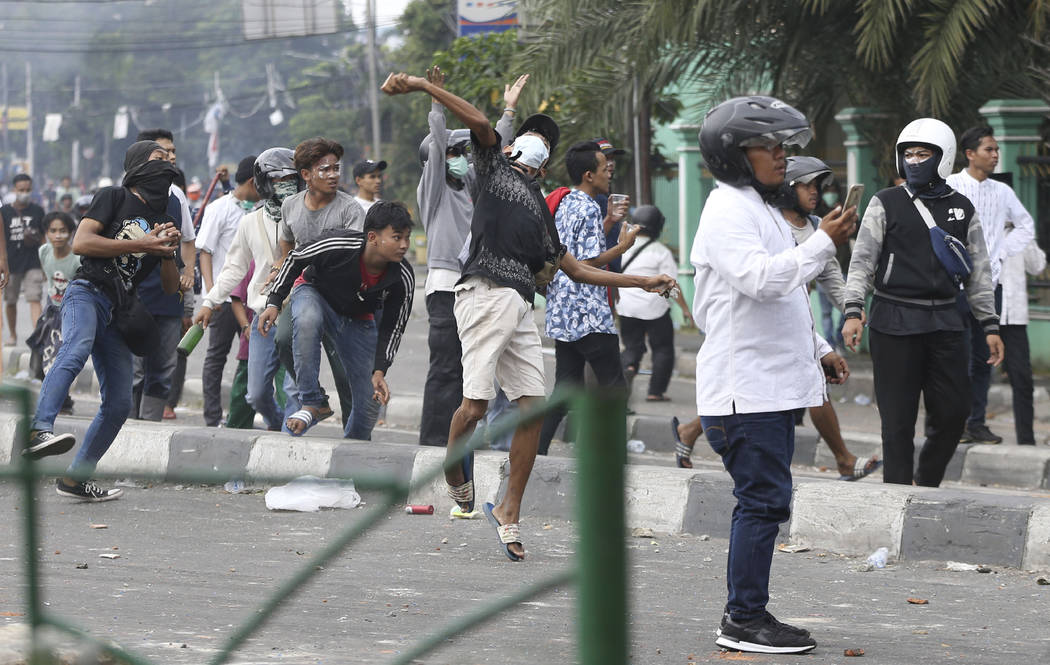Supporters of the losing presidential candidate throw rocks at police Wednesday, May 22, 2019, ...