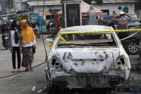 Muslim women walk near a burnt car in Jakarta, Indonesia, Wednesday, May 22, 2019. Supporters o ...