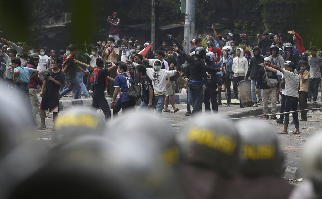 Supporters of the losing presidential candidate clash with police Wednesday, May 22, 2019, in J ...