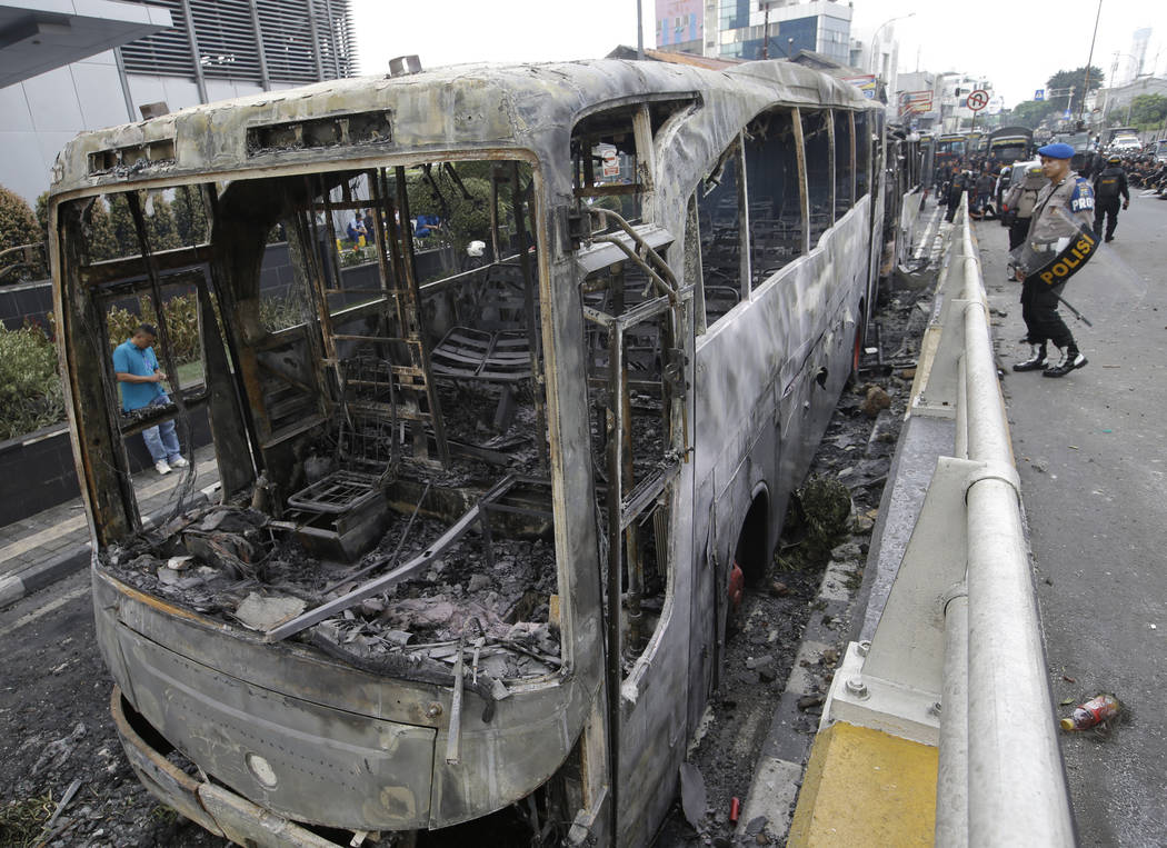 Indonesian police check burnt buses in Jakarta, Indonesia, Wednesday, May 22, 2019. Supporters ...