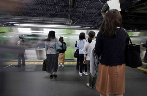 Commuters wait to get on a train at a station Wednesday, May 22, 2019, in Tokyo. A police-devel ...
