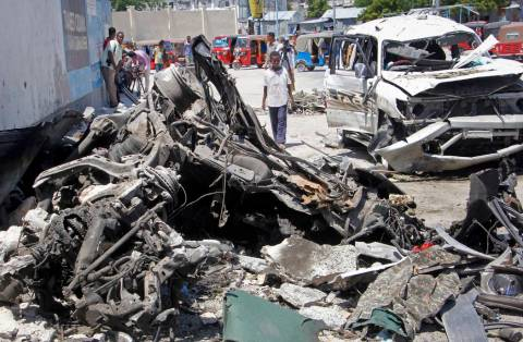 Somalis walk near the wreckage after a suicide car bomb attack in the capital Mogadishu, Somali ...