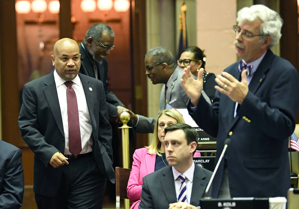 Assembly Speaker Carl Heastie, D-Bronx, left, walks on the Assembly floor as Assemblyman Andy G ...
