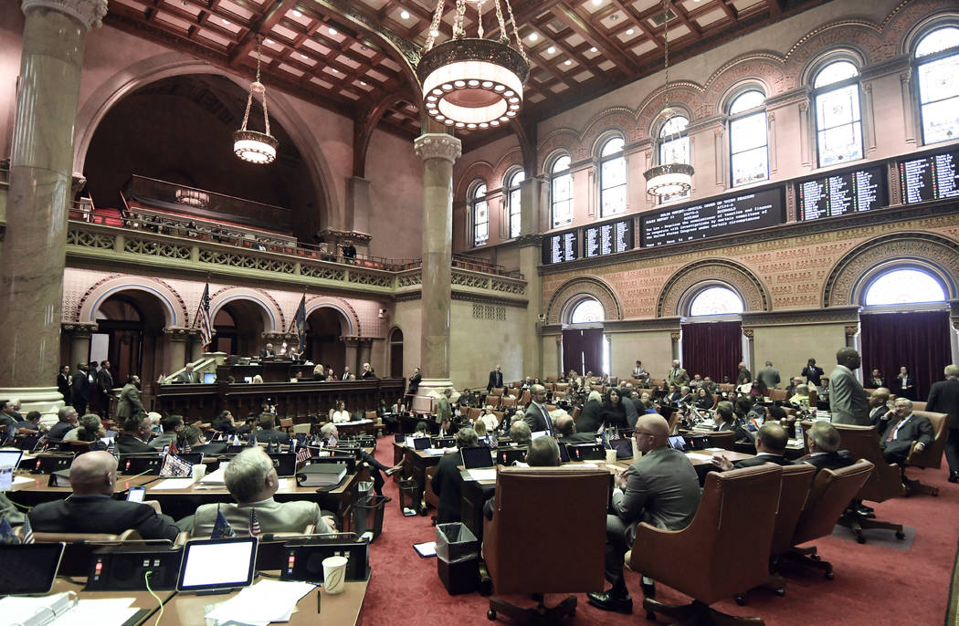 Members of the New York state Assembly vote on legislation that authorizes state tax officials ...