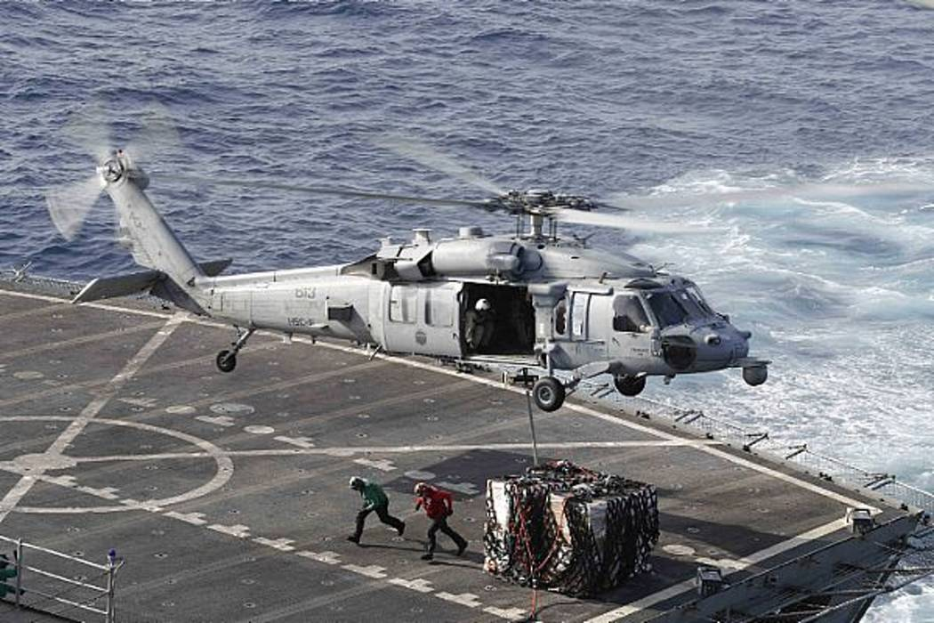 In this Sunday, May 19, 2019 photo, an MH-60S Sea Hawk helicopter transports cargo from the fas ...