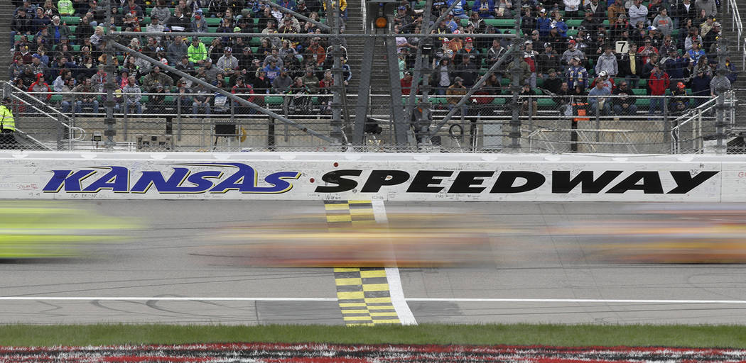 Drivers cross the start/finish line early in theNASCAR Cup Series auto race at Kansas Speedway ...