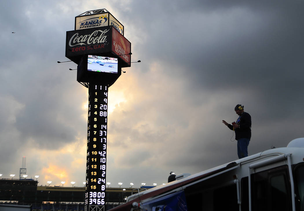 A fan follows events from the roof of a camper during the NASCAR Cup Series auto race at Kansas ...