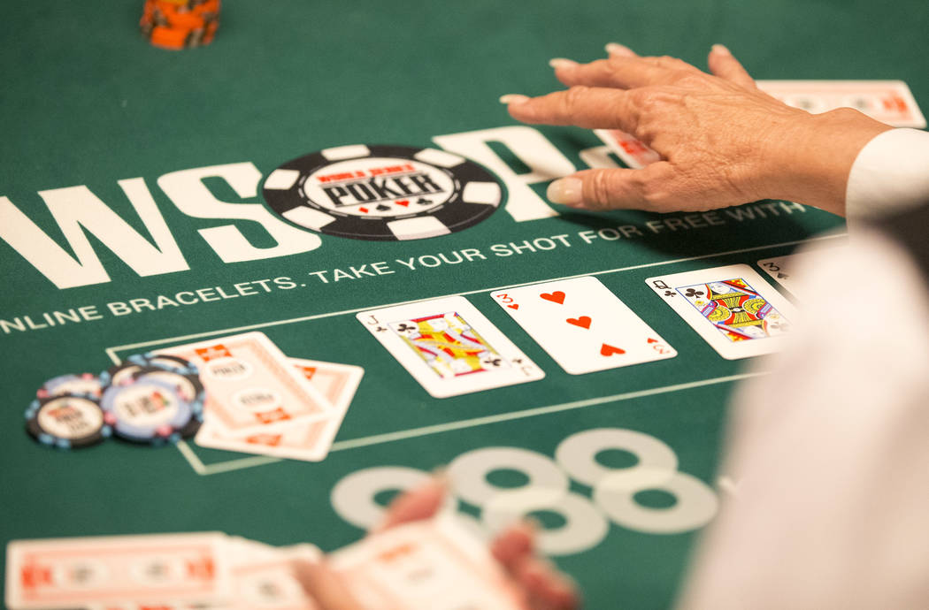 A dealer plays a hand on day one of the main event during the World Series of Poker tournament ...
