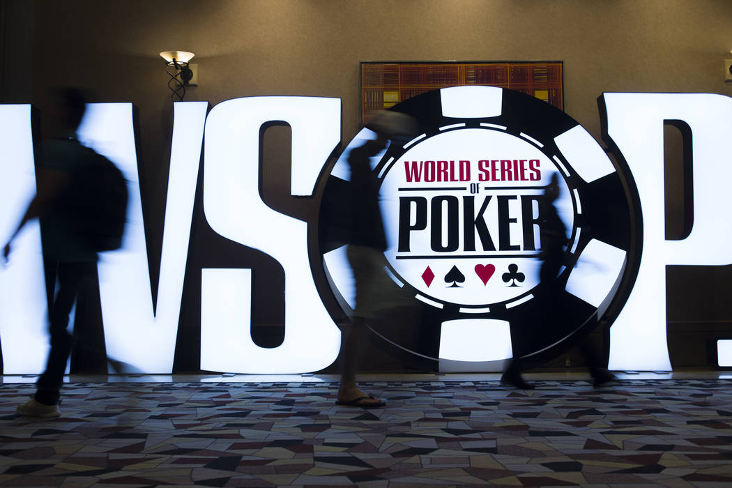 People walk past a World Series of Poker sign day five of the competition at the Rio Convention ...
