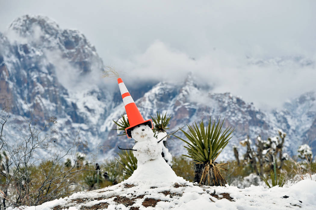 A snowman is capped with a traffic cone at the entrance at Red Rock Canyon National Conservatio ...
