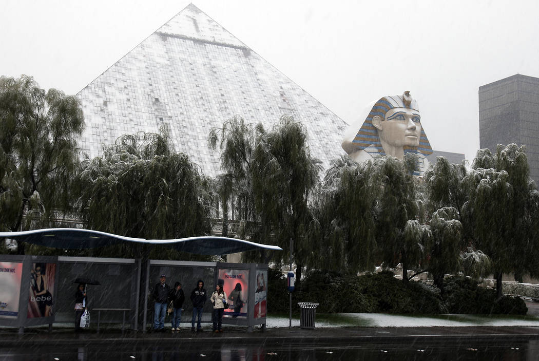 JOHN GURZINSKI/LAS VEGAS REVIEW JOURNAL NEWS----People wait for a bus as falling snow covers t ...