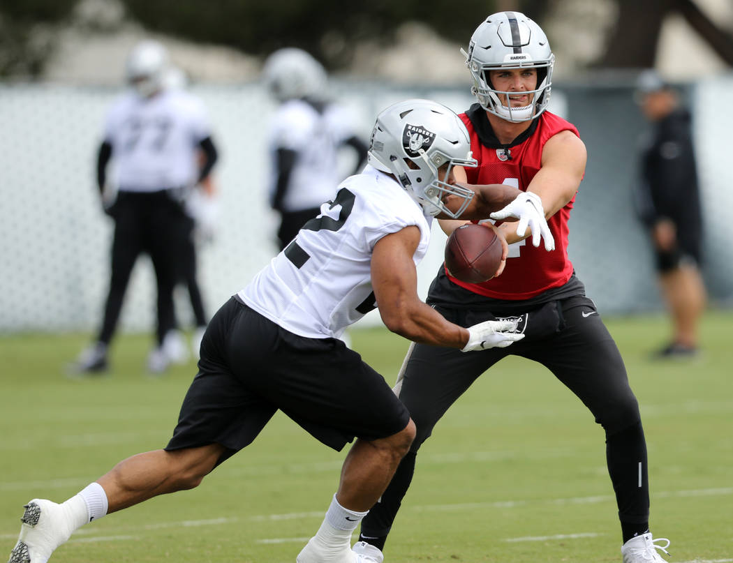 Oakland Raiders quarterback Derek Carr, right, hands off the football to running back Doug Mart ...