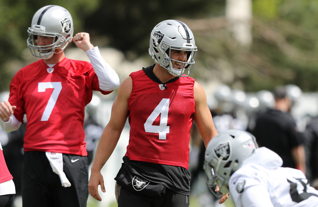 Oakland Raiders quarterback Derek Carr (4) walks on the field next to quarterback Mike Glennon ...