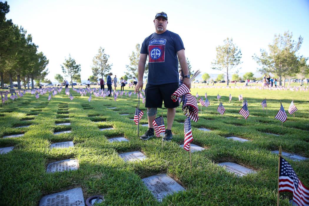 Volunteer Ernie Gonzales, U.S. Army veteran, assisting with placing American flags on gravesite ...
