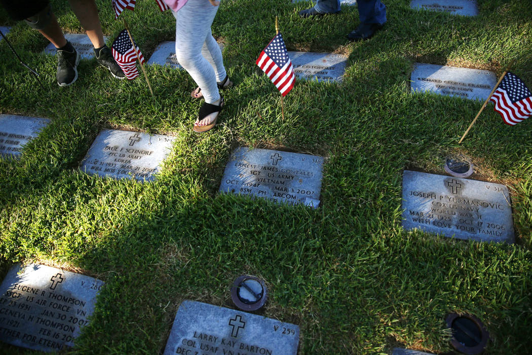"American flags decorate gravesites during the annual ""Flag-In"" event at the South ..."