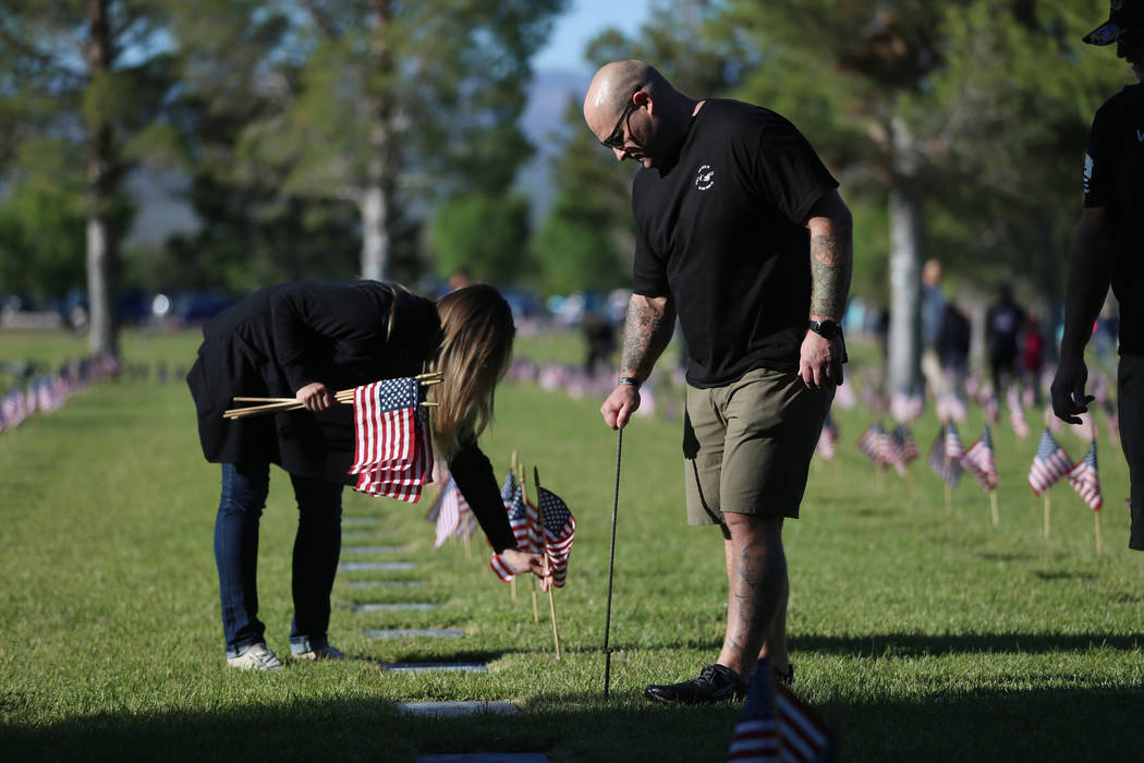Volunteers Wendy Hackman, left, and her husband Monte, U.S. Army veteran, assist with placing A ...