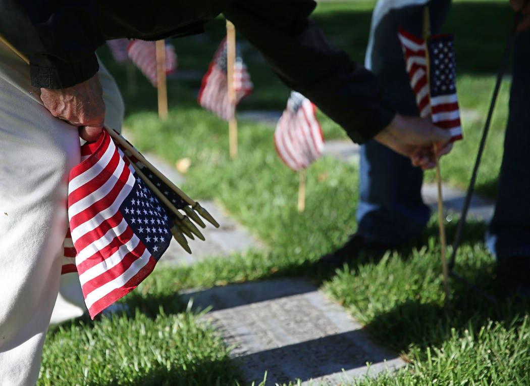 Ray Pelletier, U.S. Army veteran, places an American flag on a gravesite during the annual &#x2 ...