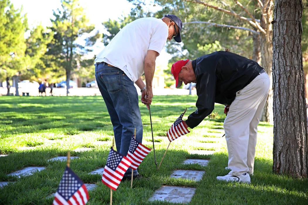 Volunteers William Wasserburger, left, and Ray Pelletier, U.S. Army veteran, place an American ...