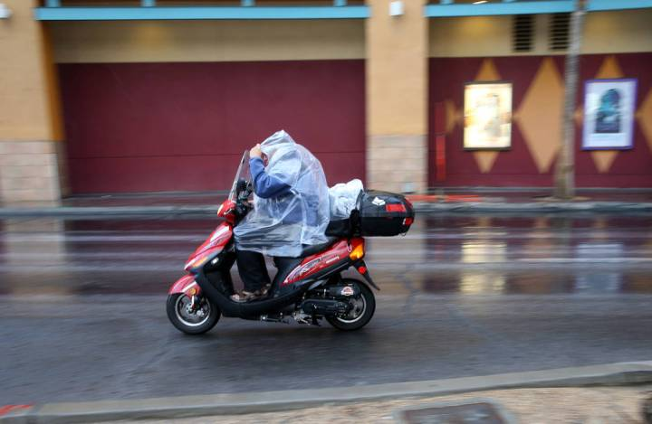 A scooter rider protects himself from a light rain on Las Vegas Boulevard near Fremont Street i ...
