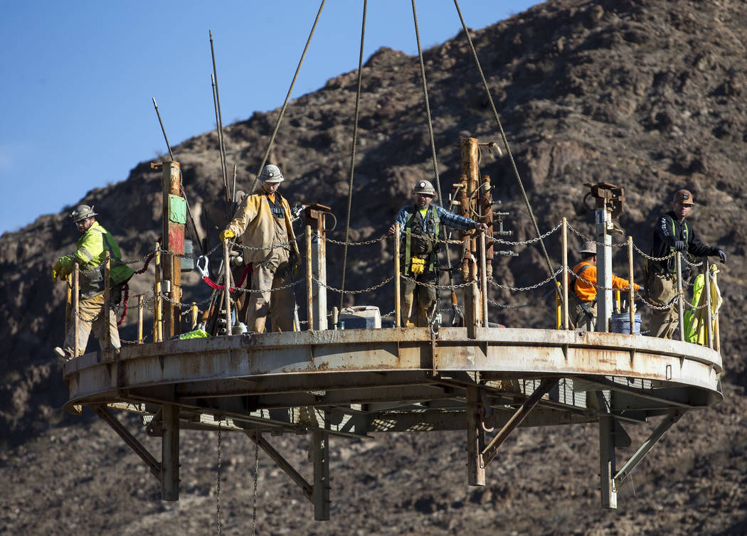 Richard Brian/Las Vegas Review-Journal Workers prepare to be lowered down the access shaft for ...