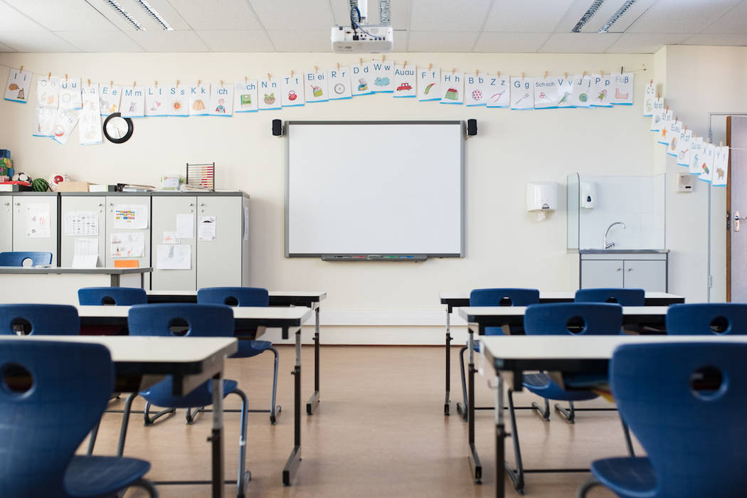 School desk and chairs in empty modern classroom. (Getty Images)