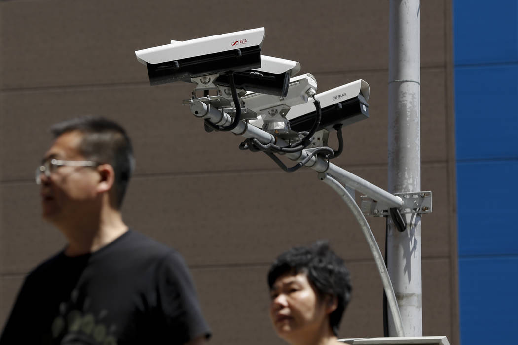 People walk by Chinese-made surveillance cameras installed along a street in Beijing, Thursday, ...