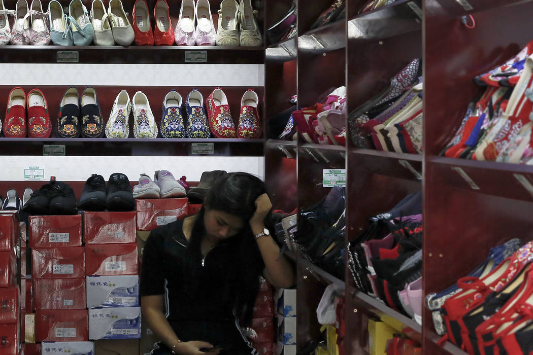 A worker browses her smartphone inside a shop selling shoes in Beijing, Thursday, May 23, 2019. ...