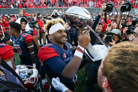 Fresno State quarterback Marcus McMaryion raises the trophy in celebration of his team's win ov ...