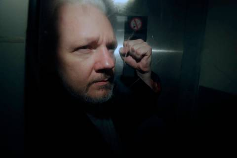 FILE - In this May 1, 2019, file photo, WikiLeaks founder Julian Assange puts his fist up as he ...