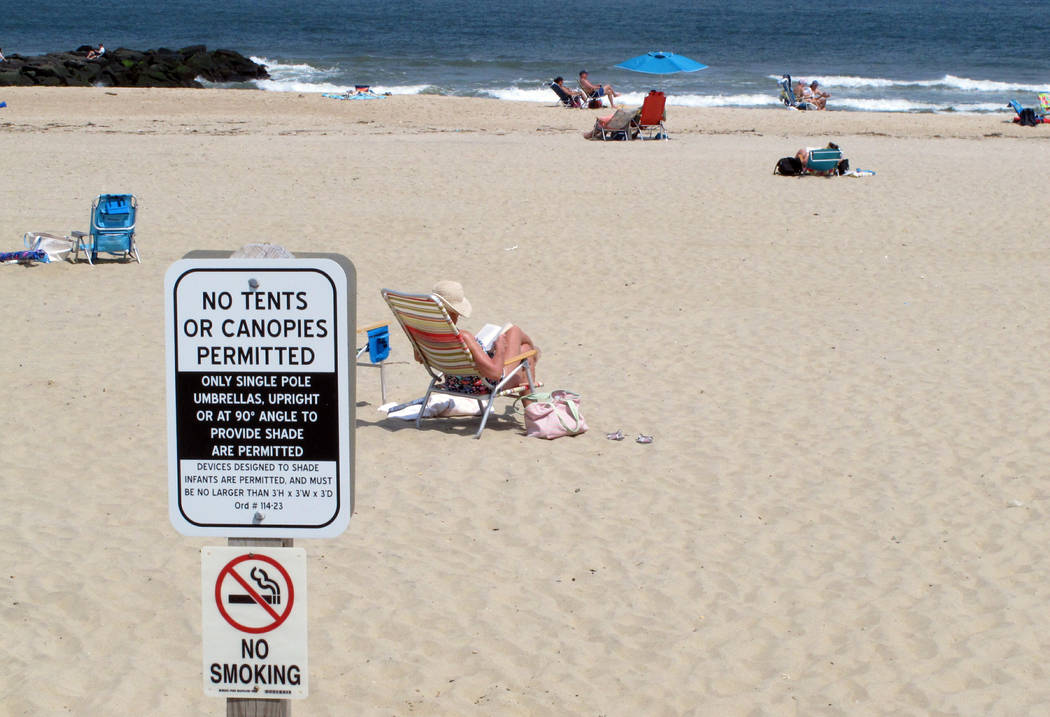 In this Monday, May 20, 2019 photo, beachgoers sit on the sand beyond a sign indicating that sm ...