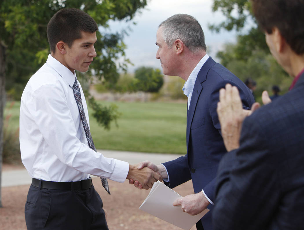 Gabriel Pence, 17, shakes hands with Tom Kovach, the executive director of the LVMPD Foundation ...