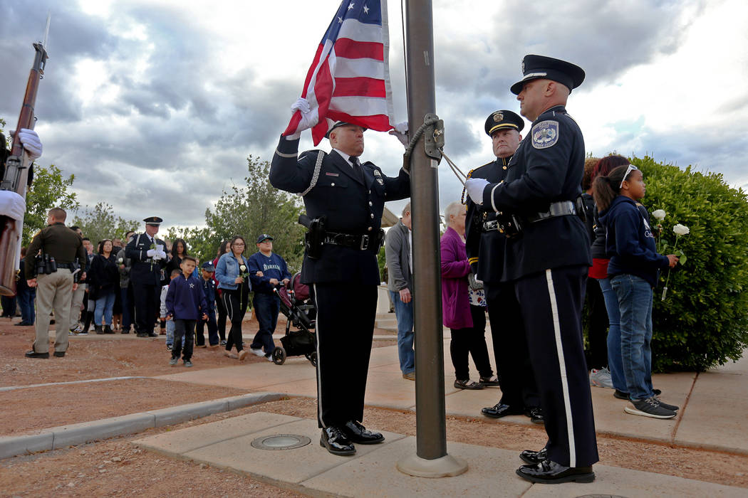 The color guard prepare to lift the flag to half mast as families of fallen officers walk behin ...