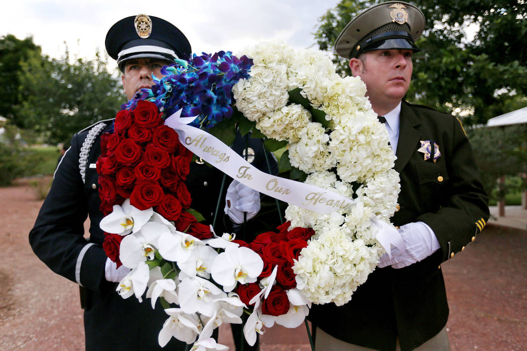 Officers hold flowers for the Southern Nevada Law Enforcement Officers memorial service at Poli ...