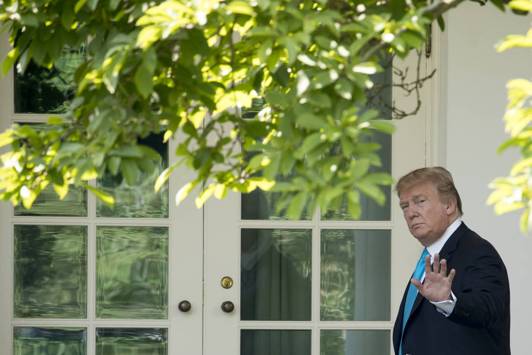 President Donald Trump waves as he walks towards the Oval Office in Washington, Thursday, May 2 ...