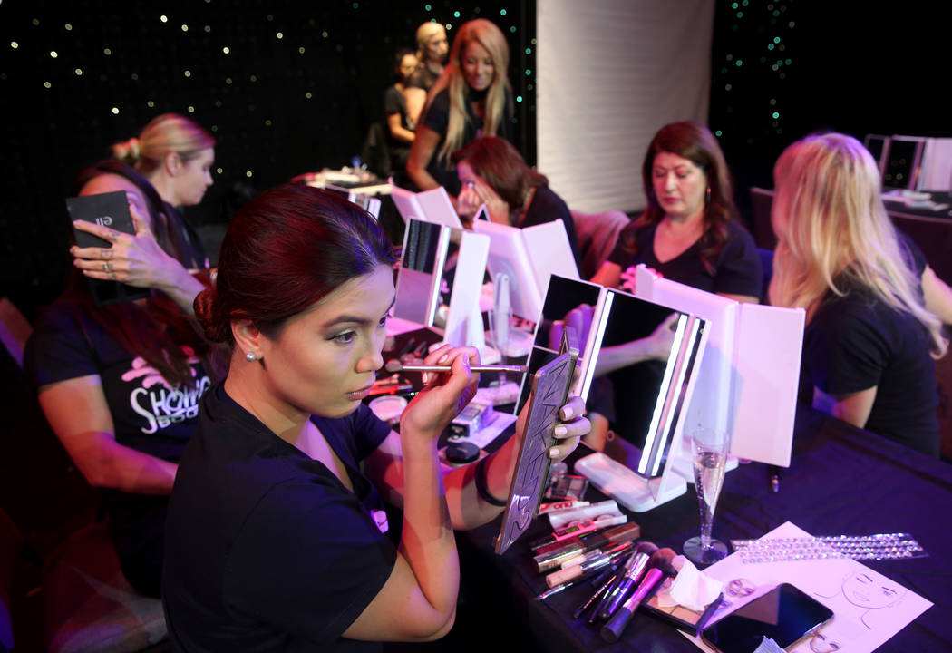 Marianne Tanada of Henderson applies makeup during a preview of Showgirl Bootcamp at Saxe Theat ...