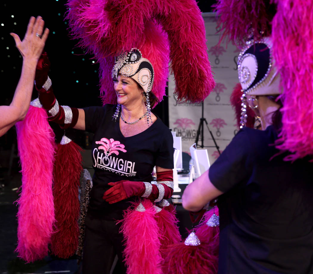 Marla Laughlin of Las Vegas gets a high-five after doing the showgirl walk during a preview of ...