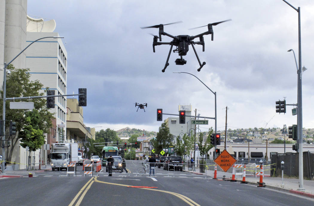 In a May 21, 2019 photo, two drones fly above Lake Street in downtown Reno, Nev., on, as part o ...